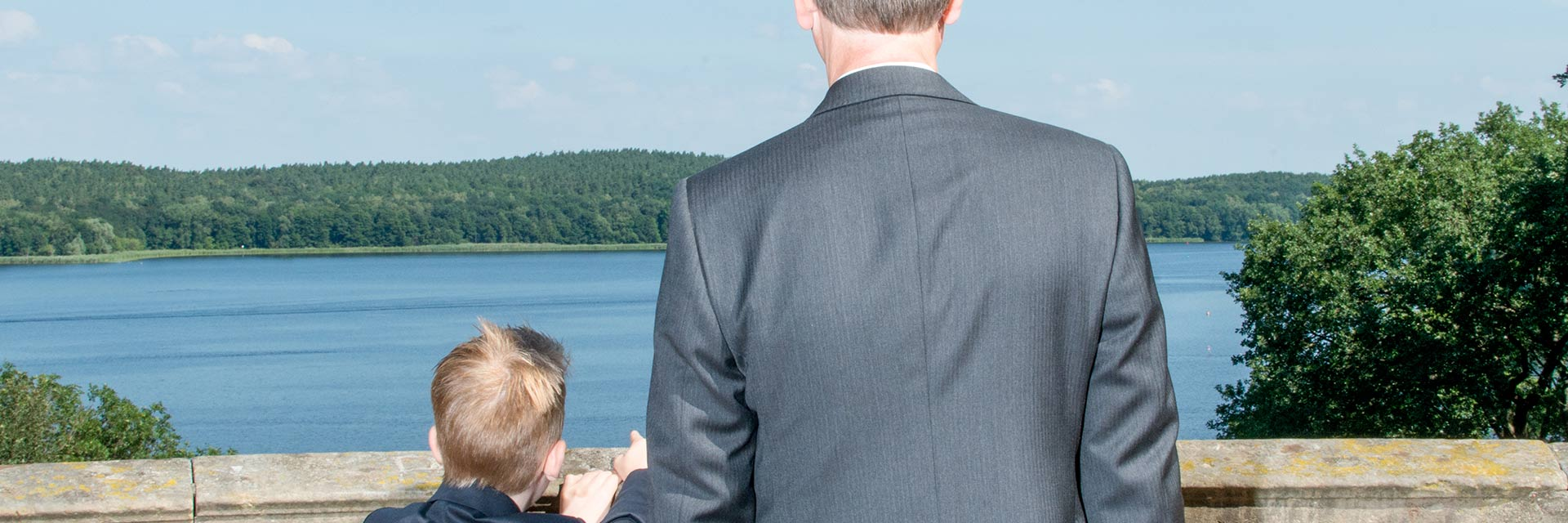 A man and his son, both in suits, look out over a body of water.