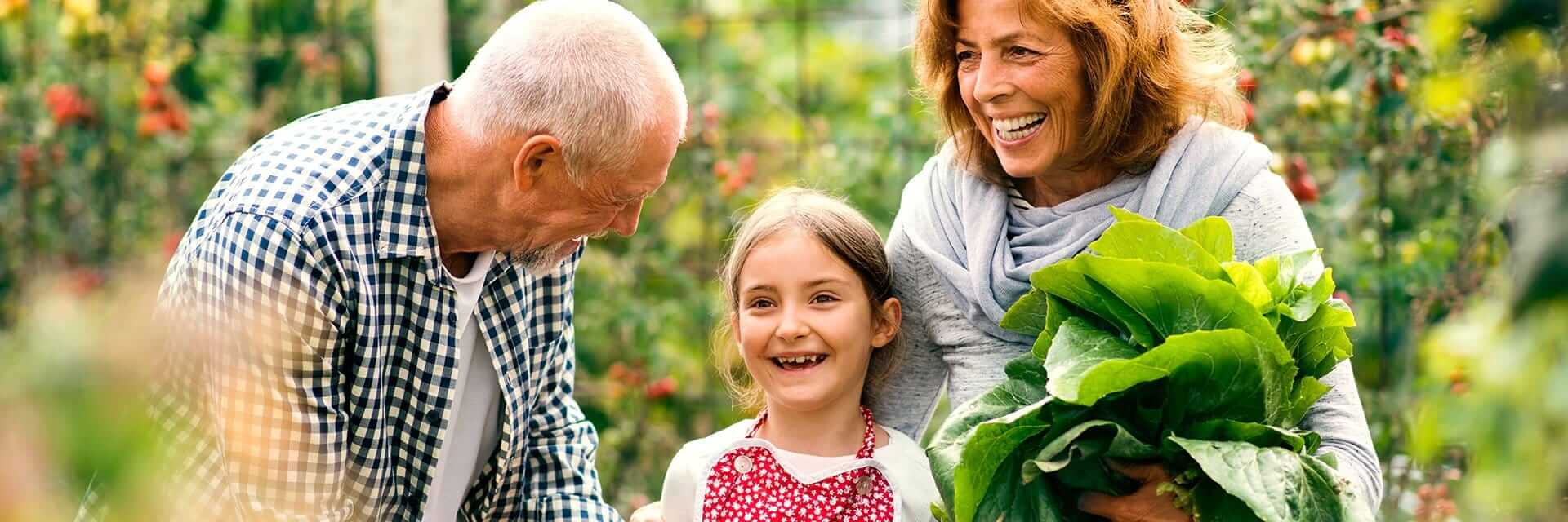 Retired couple walking through their garden with their granddaughter.