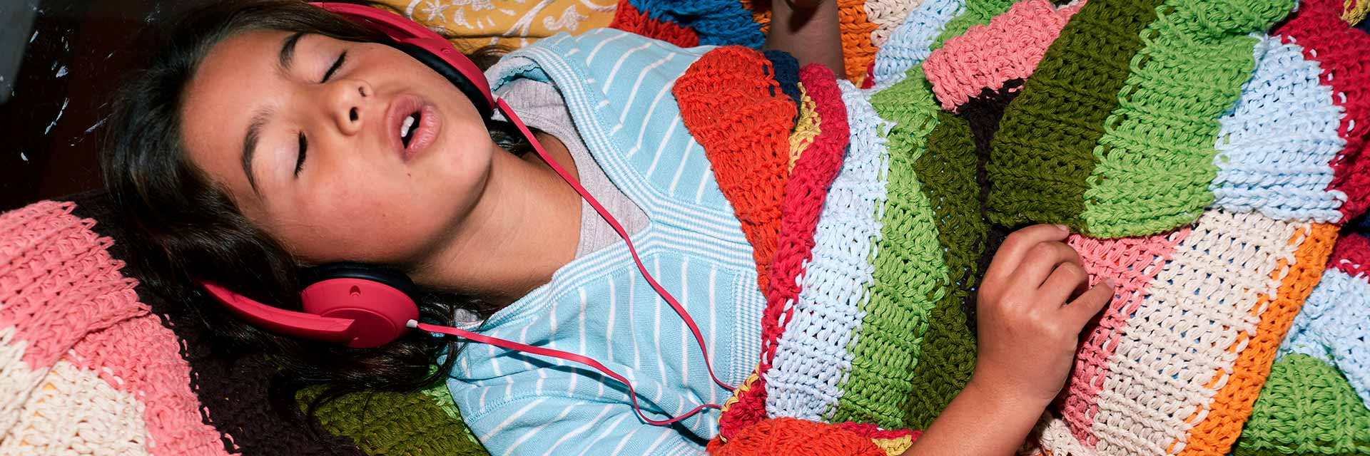 A young girl listens to music through headphones while snuggling with a blanket.