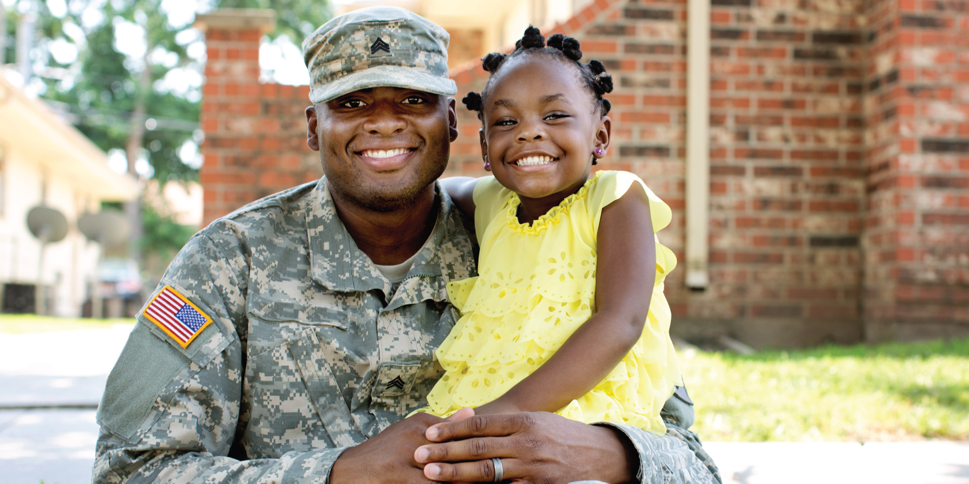 A man in a military uniform squats and smiles with his daughter on his knee.
