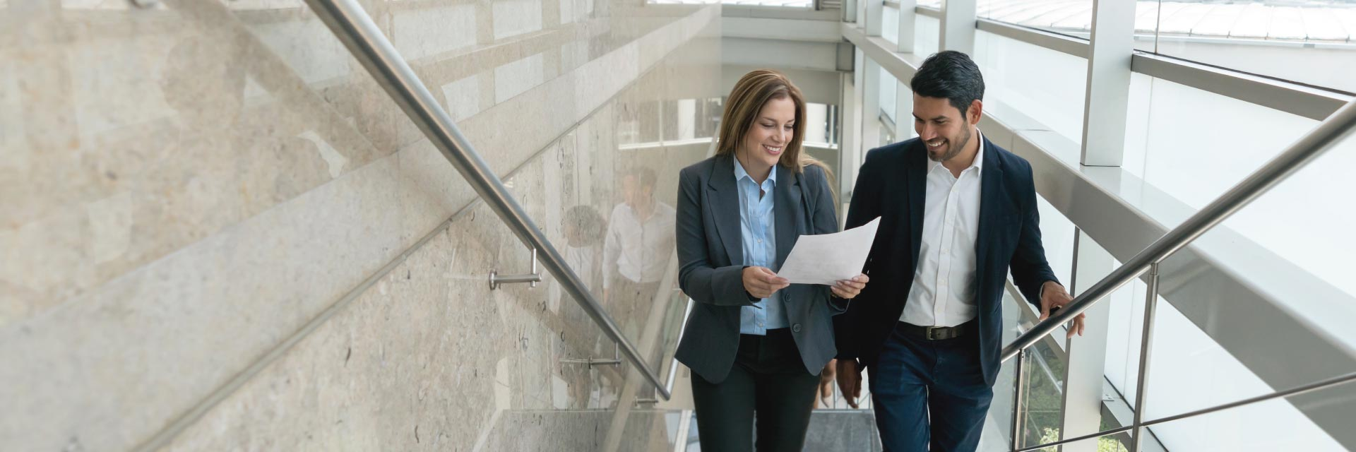 Two financial professionals review a document while walking up a flight of stairs.