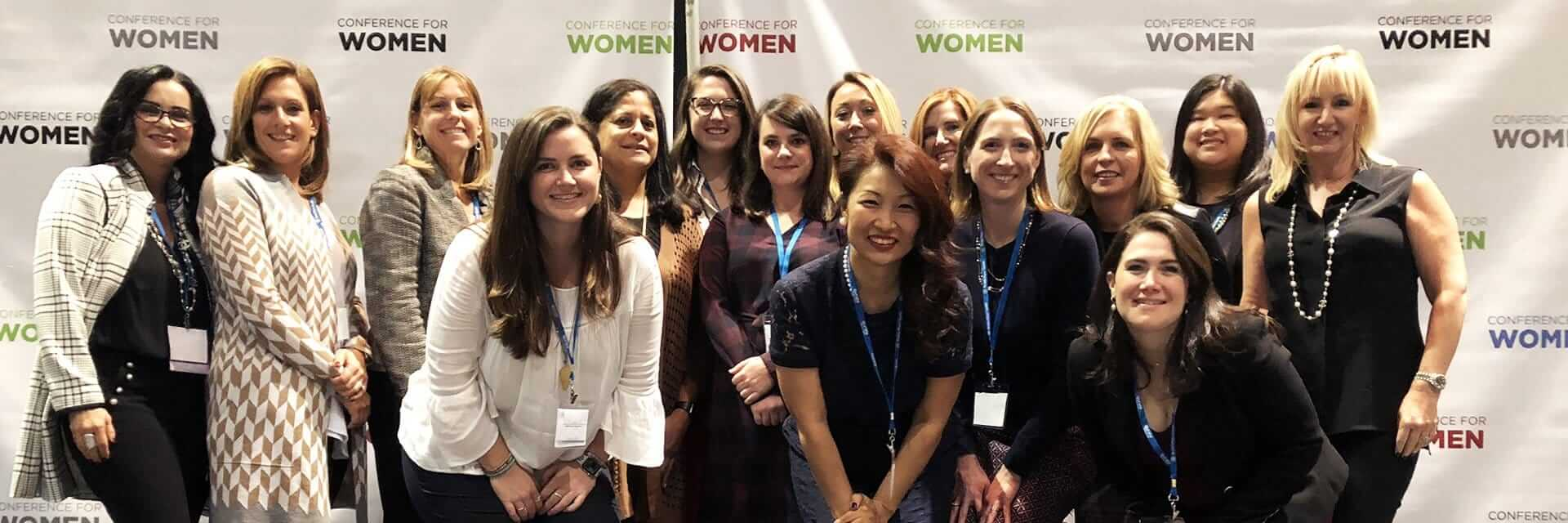 Group of female Penn Mutual associates pose for a photo in front of an advertisement banner during an event.