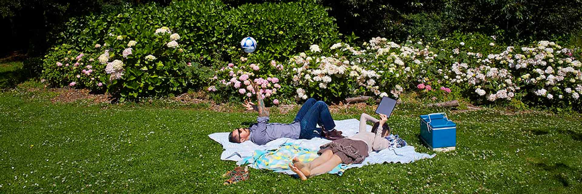A man and woman lay on a picnic blanket in a park.