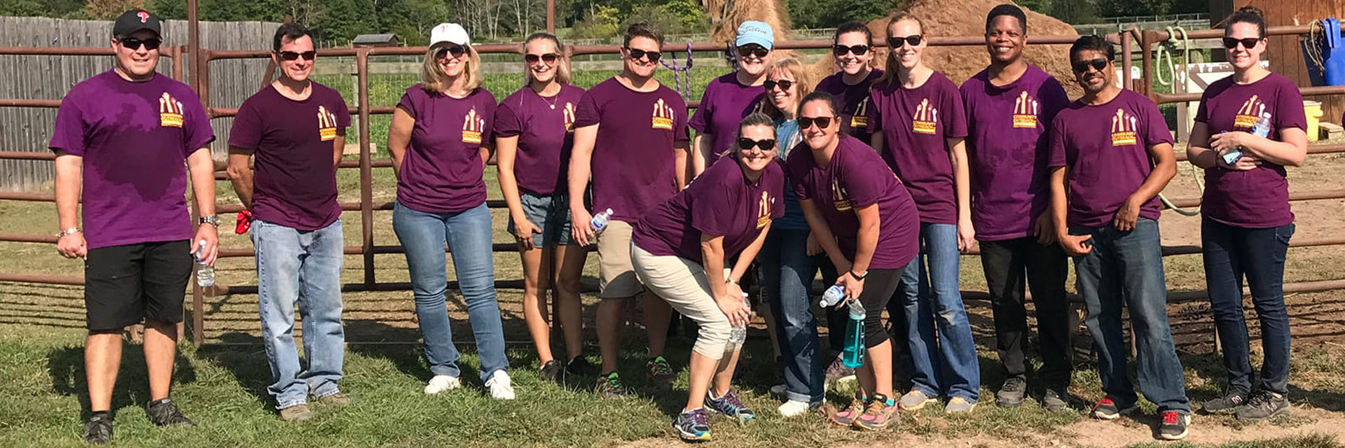 A large group of Penn Mutual associates, in purple shirts, posing together on a farm.